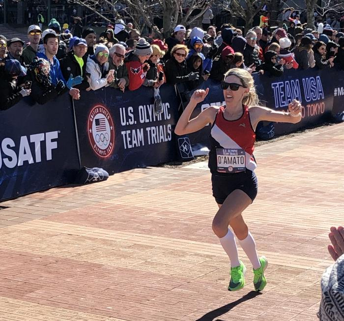 Keira D'Amato celebrates her finish at the 2020 U.S. Olympic Marathon Trials as spectators cheer her to the finish.